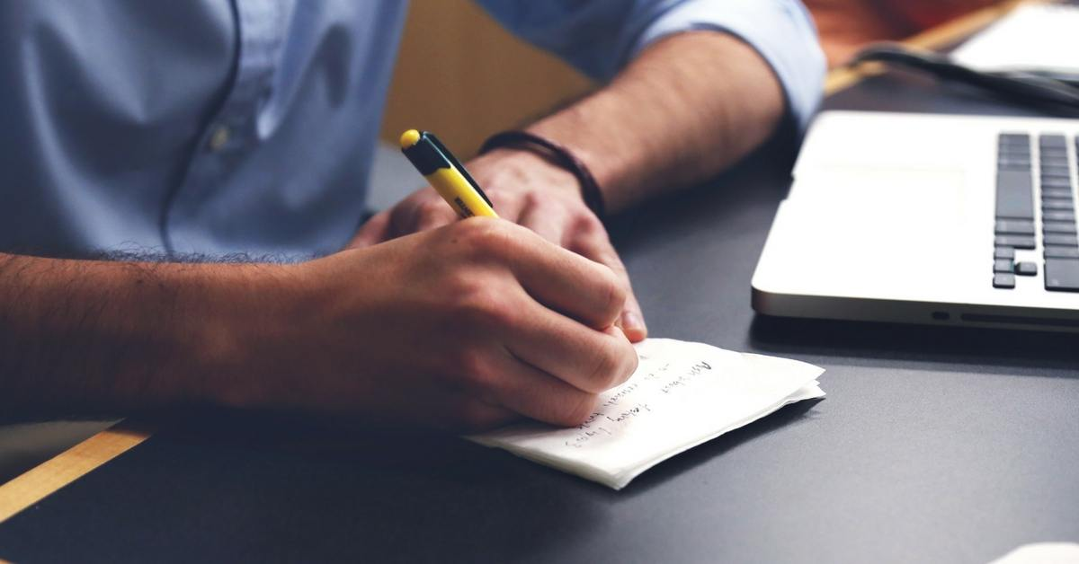 Person writing notes with notepad and pencil